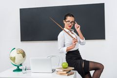 young teacher in stockings with pointer sitting on desk in front royalty free stock image