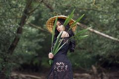 Young Vietnamese girl in a straw hat in a tropical forest stock photos