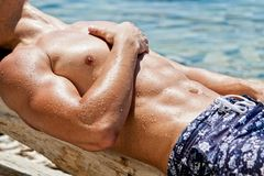 Young sexy wet guy lying on the beach Stock Images