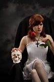 Young witch with a skull and rose stock photo