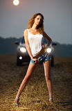 Young sexy woman. In car headlights Royalty Free Stock Photos
