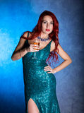 Young sexy woman with big boobs in blue elegant dress holding wineglass with champagne.  Royalty Free Stock Photo