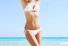Young and sexy woman in a bikini on the beach. Beautiful woman in a bikini. Young and sporty girl posing on a beach at summer Royalty Free Stock Photography