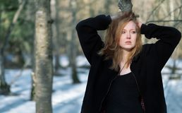 Young sexy woman in black clothes,with red hair, looking sad, in the winter forest royalty free stock photos