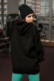 Young Sexy Woman In Black Jacket With Hood. Young Sexy Woman In Black Hooded Sweatshirt Posing In Gym Royalty Free Stock Photos