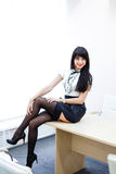 Young sexy woman in black stockings sitting on a table in  offic Stock Photo