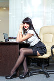Young sexy woman in black stockings sitting on workplace in  off Royalty Free Stock Image