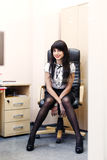 Young sexy woman in black stockings sitting on workplace in offi Stock Image