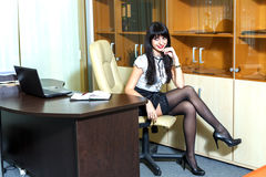 Young sexy woman in black stockings sitting on workplace in the Royalty Free Stock Photos