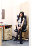 Young sexy woman in black stockings sitting on workplace in the Stock Image