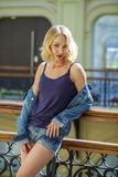 Young sexy woman in blue jeans short in the shop Stock Photography