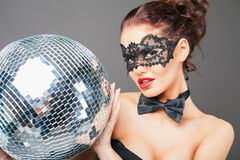 Young sexy woman in carnival mask keeping disco ball Royalty Free Stock Photos