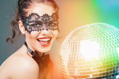 Young sexy woman in carnival mask keeping disco ball Royalty Free Stock Photo