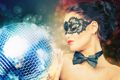 Young sexy woman in carnival mask keeping disco ball Stock Photos