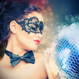 Young sexy woman in carnival mask keeping disco ball Royalty Free Stock Photography