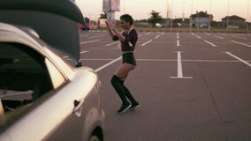 Young woman in the crop top and shorts dance twerk by the car on the parking during sunset in summertime. Moves. Slowmotion shot stock video footage