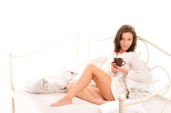 Young sexy woman with cup of coffee on bed Stock Photos
