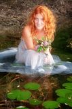 Young woman with curly red hair is sitting joyfully, with white dress happy in the water in the lake royalty free stock image