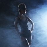 A young and sexy woman on a dark and foggy background Stock Image