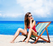 Young and sexy woman in a deckchair on the beach Stock Image