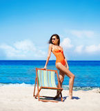 Young and sexy woman in a deckchair on the beach. Hot, young woman with perfect legs posing on the beach nearby sun lounge Stock Photo