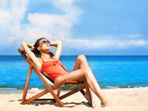 Young and sexy woman in a deckchair on the beach Royalty Free Stock Images