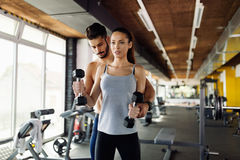 Young sexy woman doing exercises in gym with trainer. Young sexy women doing exercises for biceps in gym with trainer Royalty Free Stock Photos