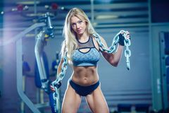 Young sexy woman doing exercises with heavy chain in gym. Classic bodybuilding. Muscular blonde fitness woman doing. Exercises in the gym. Fitness woman in the Royalty Free Stock Photography