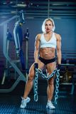 Young sexy woman doing exercises with heavy chain in gym. Classic bodybuilding. Muscular blonde fitness woman doing. Exercises in the gym. Fitness woman in the Stock Photos