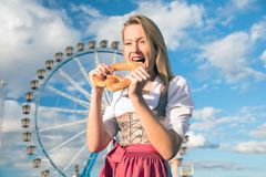 Girl with dirndl does oktoberfest wiesn in munic. Young woman is doing oktoberfest in munic bavaria in the spring summer autumn folk festival. she is wearing a stock images
