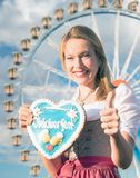 Girl with dirndl does oktoberfest wiesn in munic. Young woman is doing oktoberfest in munic bavaria in the spring summer autumn folk festival. she is wearing a stock image