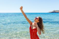 Young woman dressed in fashion swimsuit using mobile phone camera for take selfie stock photo