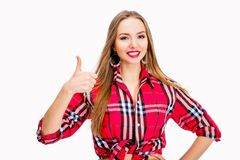 Young sexy woman dressed in jeans and checkered shirt posing in studio. Isolated on white thumb up Royalty Free Stock Photo