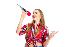 Young sexy woman dressed in jeans and checkered shirt singing. In microphone isolated on white background Royalty Free Stock Photos