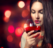Young woman drinking red wine. Beauty Young woman drinking red wine over night background royalty free stock photo