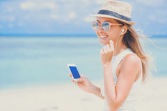 Young woman with earphones using phone on the beach. Young woman in dress, sunglasses and hat, holding phone with blue screen on ocean background, listening Royalty Free Stock Photography