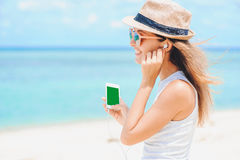 Young sexy woman with earphones using phone on the beach Royalty Free Stock Photography