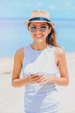 Young woman with earphones using phone on the beach. Young woman in dress and sunglasses with hat on ocean background, listening music by phone on the beach Stock Photo