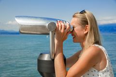 Beautiful view. Young sexy woman enjoy the view with an coin opertated binoculars in Lazise Lago di Garda. The sun is shining, the blue water, the blue sky and Stock Photo
