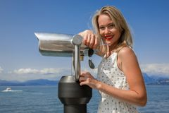 Beautiful view. Young sexy woman enjoy the view with an coin opertated binoculars in Lazise Lago di Garda. The sun is shining, the blue water, the blue sky and Stock Images