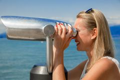 Beautiful view. Young sexy woman enjoy the view with an coin opertated binoculars in Lazise Lago di Garda. The sun is shining, the blue water, the blue sky and Stock Photography