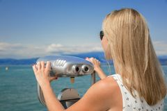 Beautiful view. Young sexy woman enjoy the view with an coin opertated binoculars in Lazise Lago di Garda. The sun is shining, the blue water, the blue sky and Stock Image