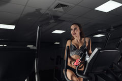 Young sexy woman during exercise on bike at gym. Copyspace. Stock Photography
