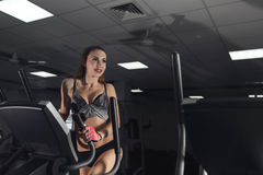 Young sexy woman during exercise on bike at gym. Copyspace. Royalty Free Stock Images
