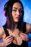 Young woman or girl dj with dark hair on pretty serious face in black shirt with musical stereo headphones or stock photo
