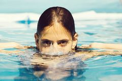 Sexy woman in swimming pool. Young sexy woman or girl with pretty face and wet hair swimming in pool with blue water sunny summer day outdoor stock image
