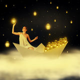 Young woman goddes in night sky. Young woman goddess floating on clouds in a paper boat and hanging stars in night sky stock photos