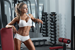 Young sexy woman in the gym. Young sexy woman dressed in white clothes in the gym Royalty Free Stock Photography