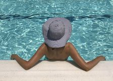 Young woman in hat relaxing at the pool royalty free stock photos