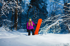 Young woman with her snowboard in the winter forest Stock Photo
